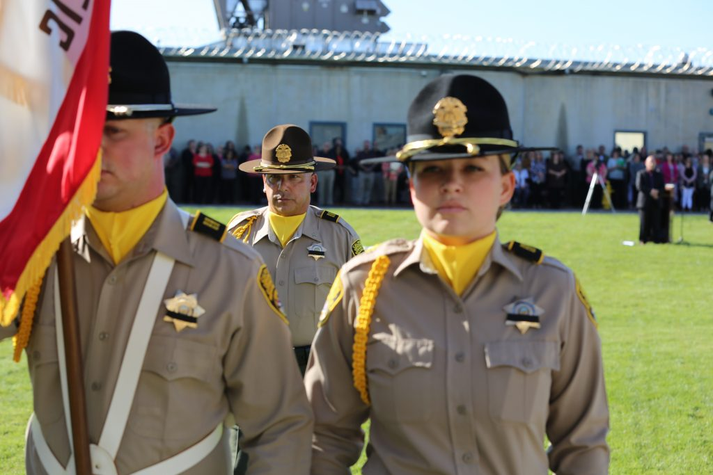 Men and women in correctional uniforms carry a flag.