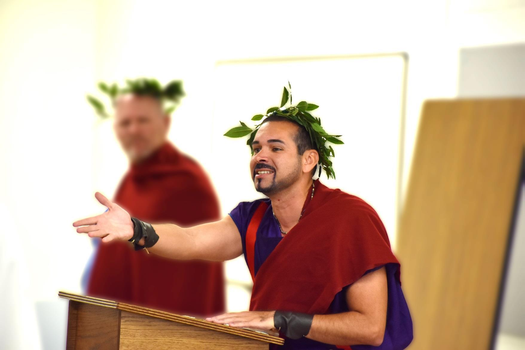 Men wear togas, while one gestures to the audience.