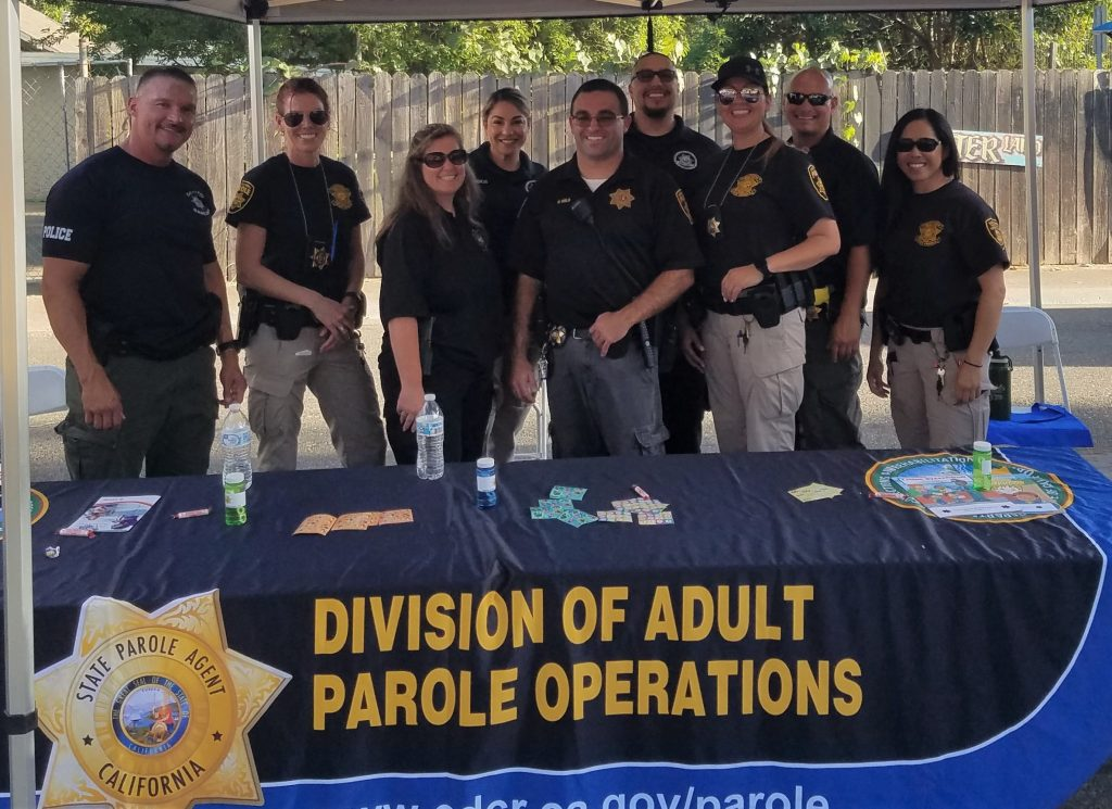 Men and women in parole agent uniforms stand behind table that says Division of Adult Parole Operations.