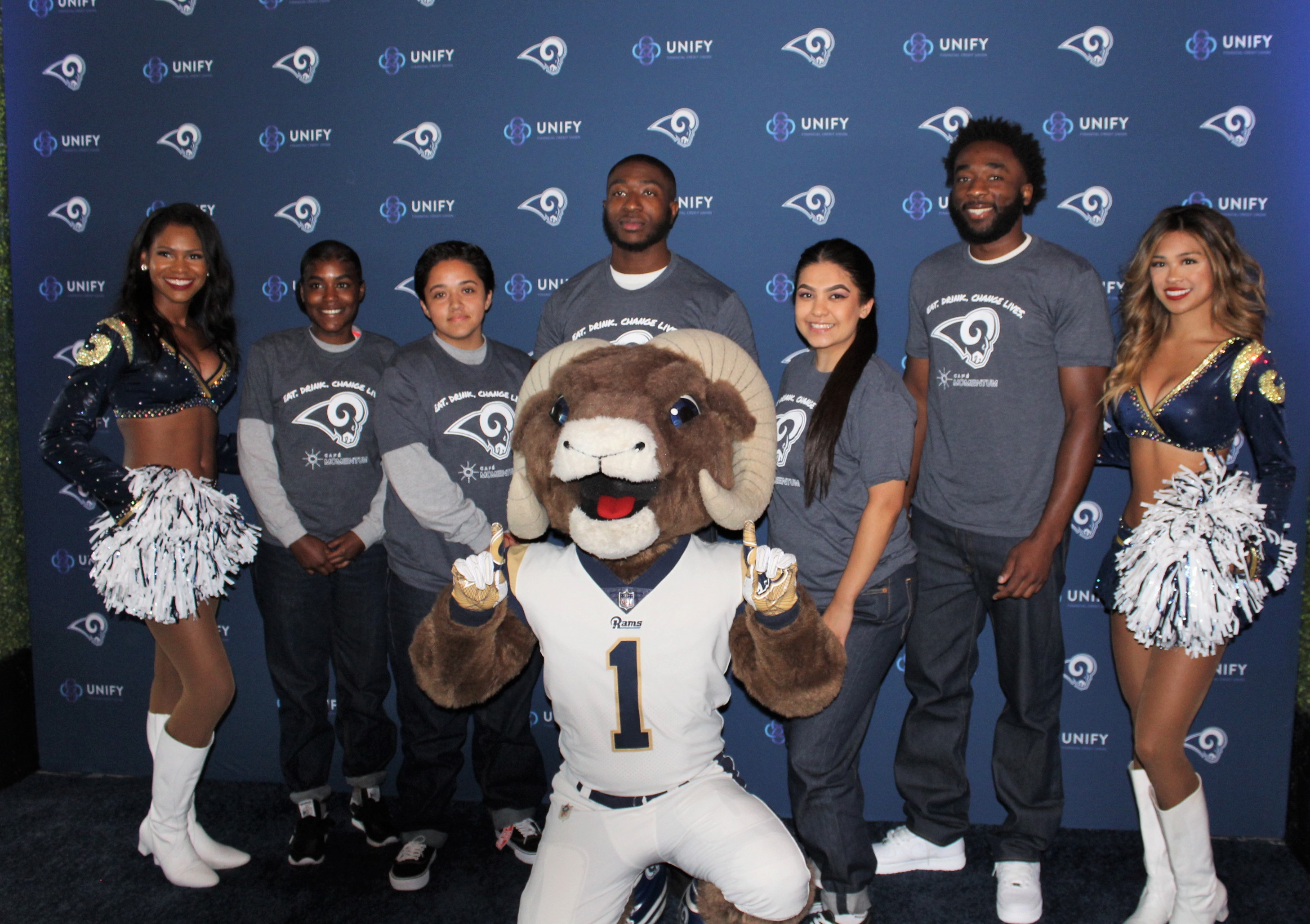 Football team mascot and two cheerleaders flank five youth.
