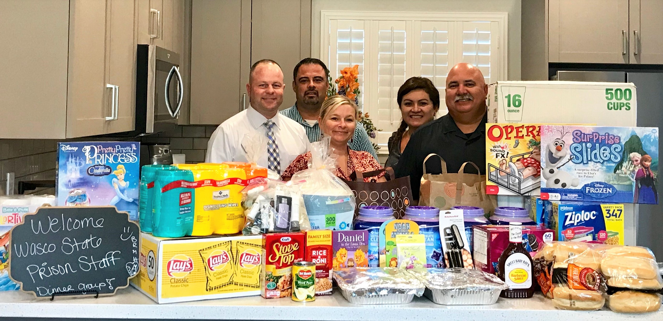 People stand behind large pile of food, kitchen supplies and games.