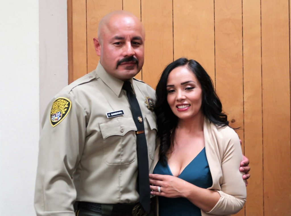 Man in correctional officer uniform poses with his wife.