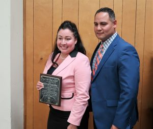 Woman in pink blazer and man in suit and tie pose for a photo. She is holding a plaque.