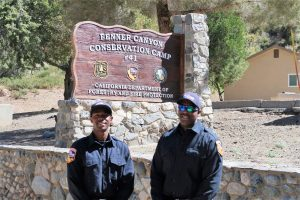 Two men in CAL FIRE uniforms stand in front of sign for Fenner Canyon Conservation Camp.