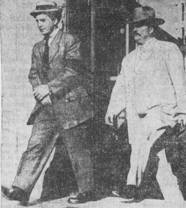 Old grainy newspaper photo shows man in handcuffs being escorted out of a jail by a man in light clothing.