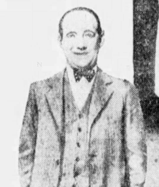 Grainy newspaper photo of man in bowtie, vest and jacket.