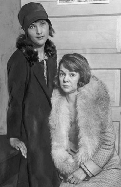 Young woman standing, leaning against a table, and another woman in a fur coat is sitting.