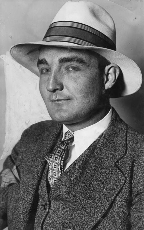 Man in hat and tie smiles at the camera.