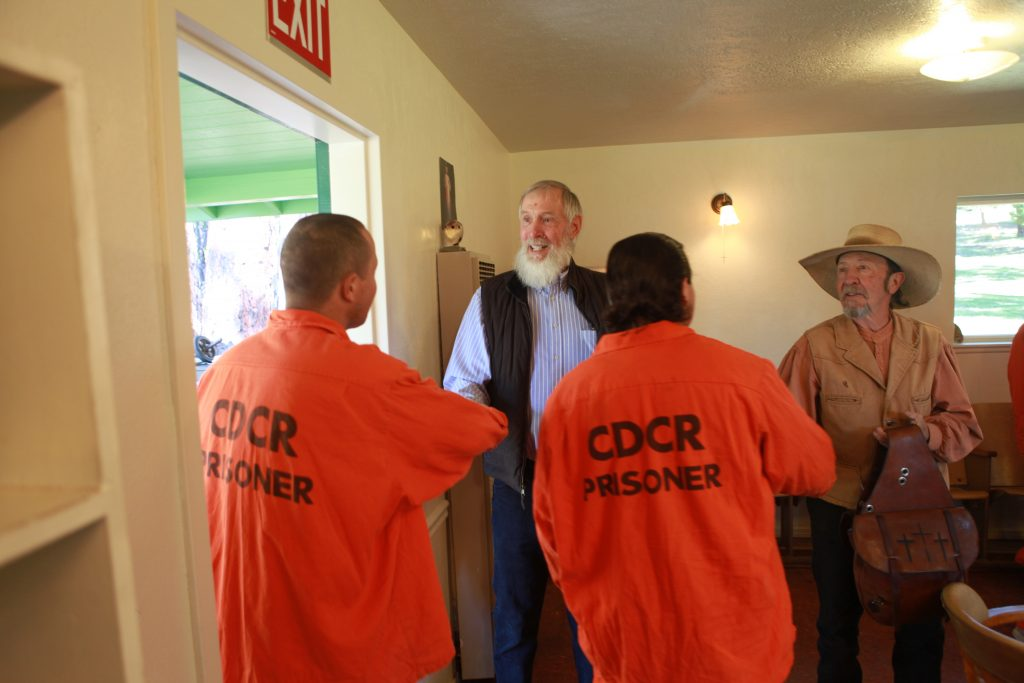 Two men shake hands with men in orange jumpsuits with words CDCR Prisoner written on their backs.
