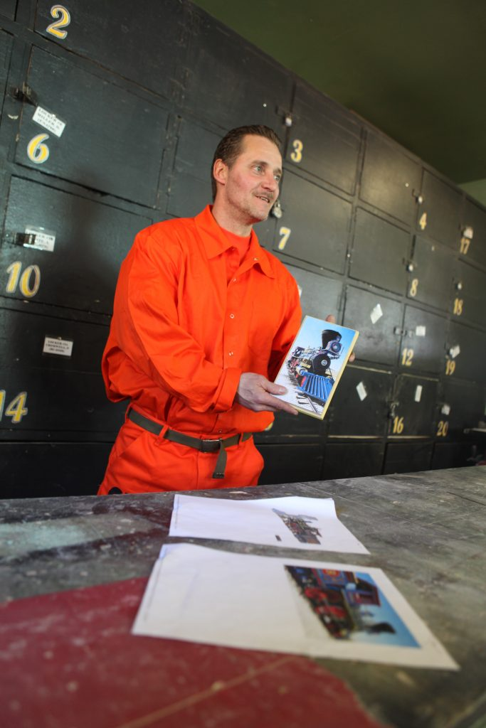 Man in orange jumpsuit holds photograph of a train. Lockers line the wall behind him.