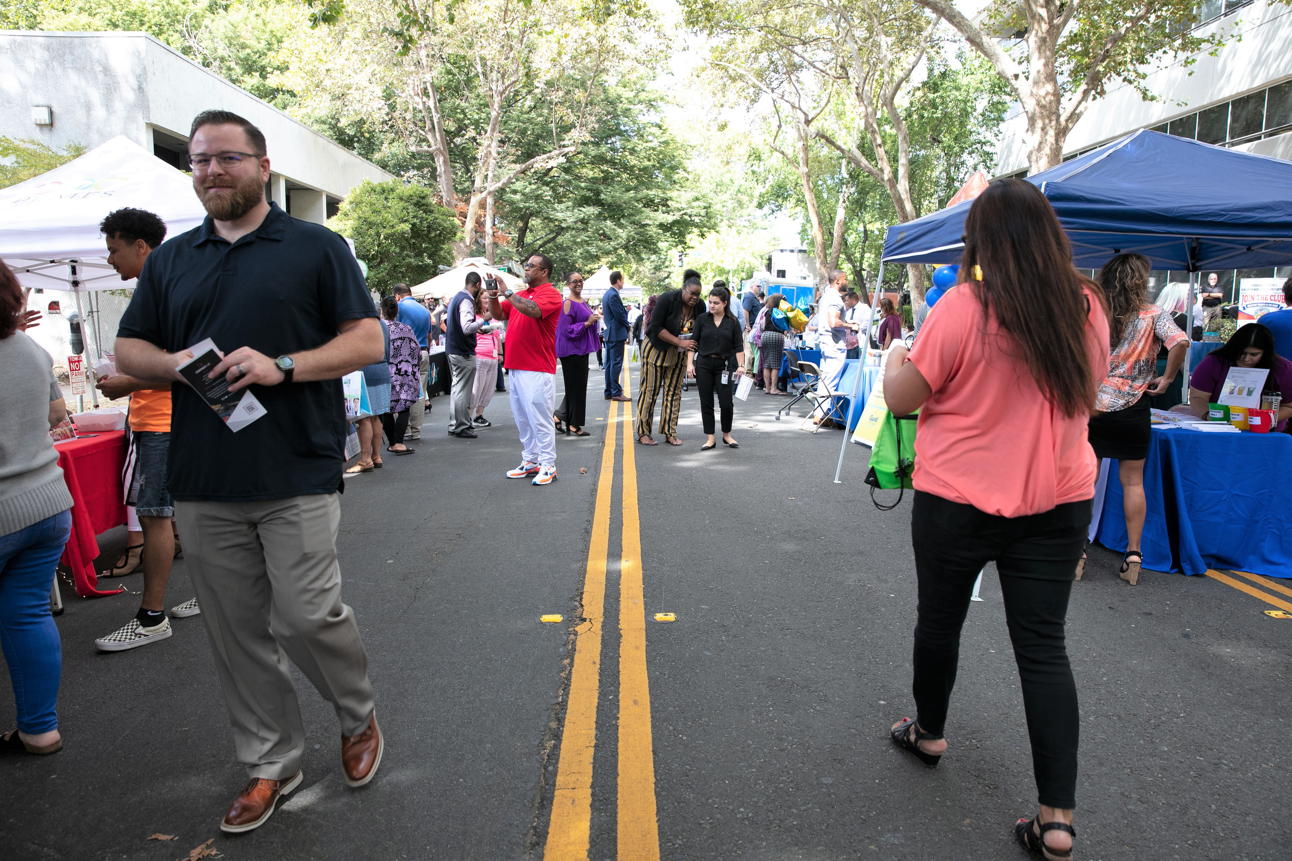 Men and women walk along a street lined with pop-up tents.