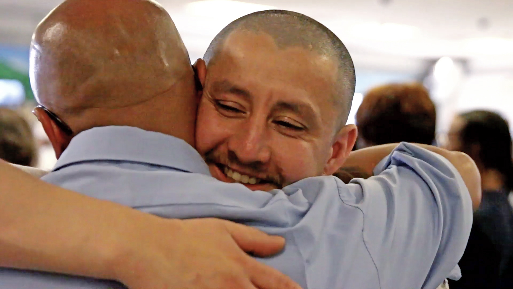 Two men hug.