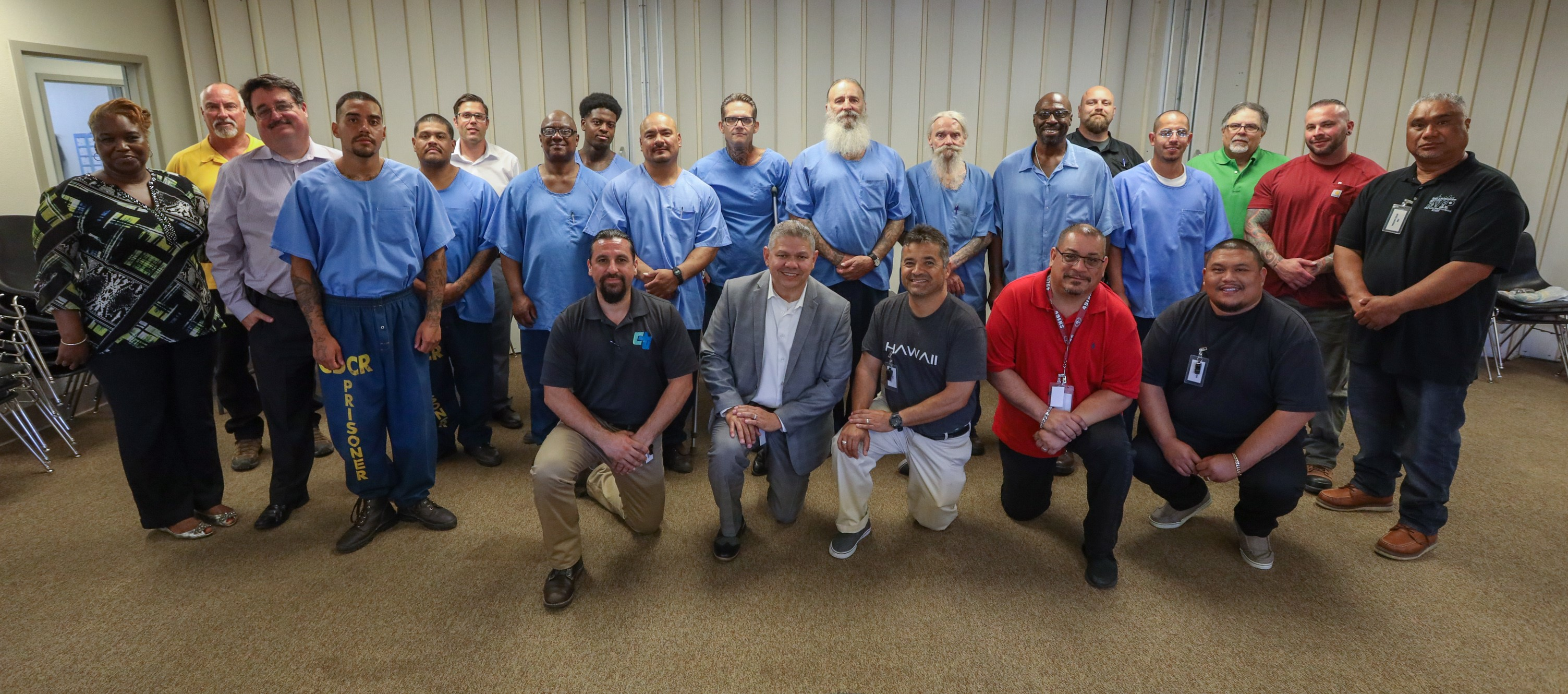 Inmates stand behind prison staff members.
