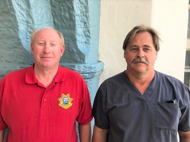 Man in red shirt and man wearing scrubs.