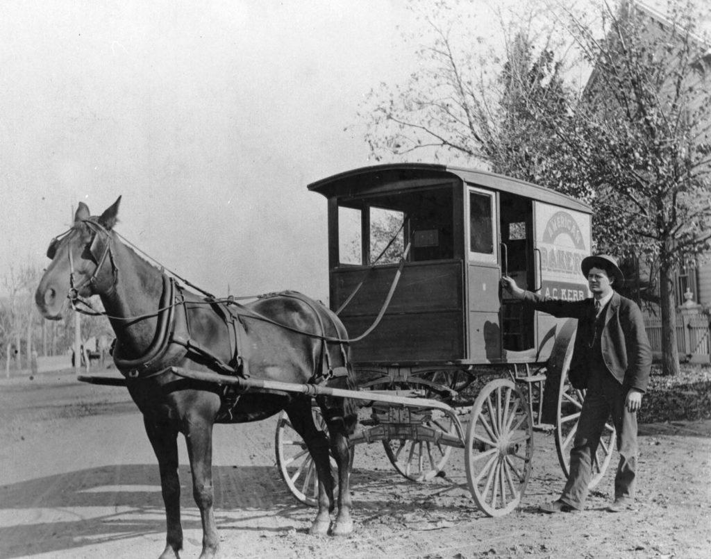 Horse drawn bakery wagon and man.