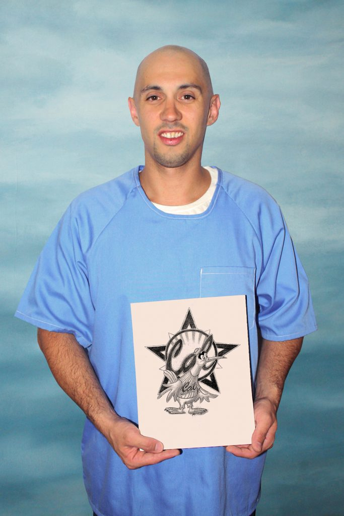 Man in blue inmate shirt hold a seagull drawing.