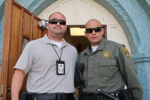 A man in uniform stands beside another man who is wearing a lanyard.