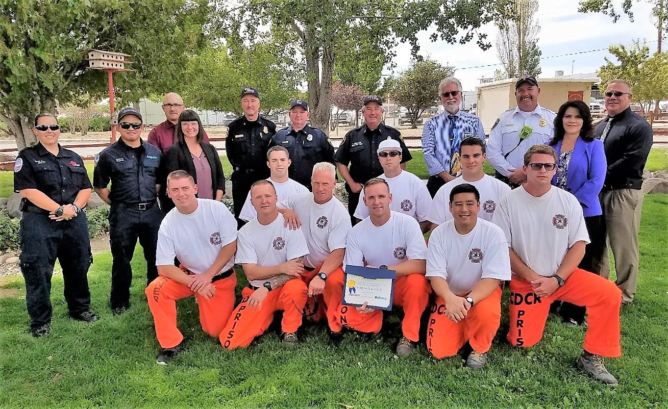 Inmates wearing orange and white sit on the ground while one holds a certificate of thanks. Standing around them are people in business attire and uniforms.