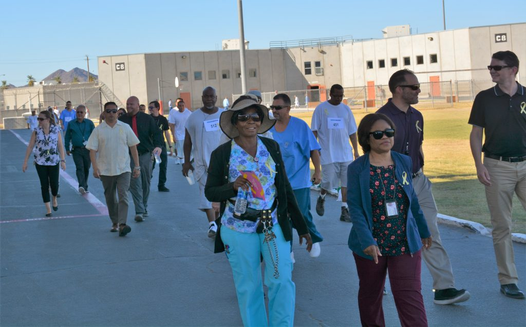 Prison staff walk along a path with inmates inside a prison.