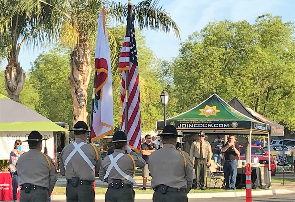 Men and women in uniform stand at attention while holding flags.