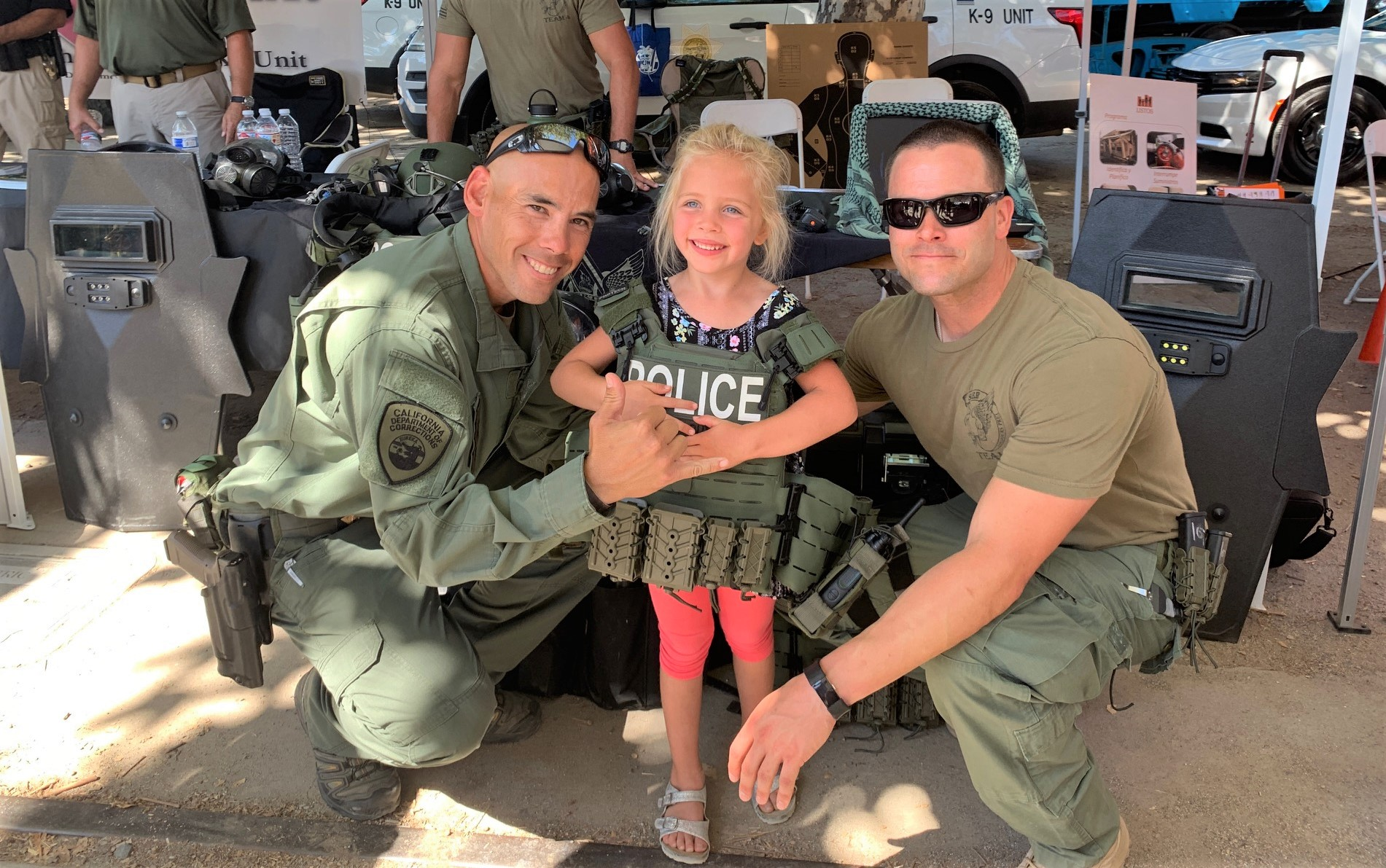 Two men in uniform and a young girl wearing some tactical gear.