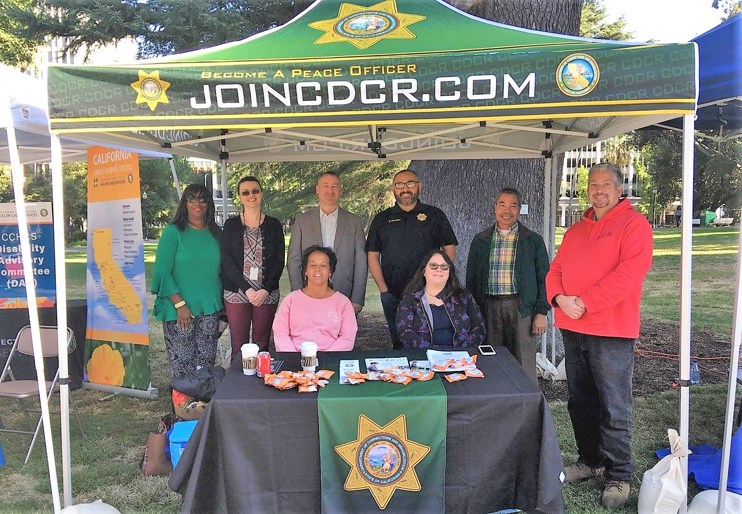 People stand under a shade cover that has the CDCR logo and the words JoinCDCR.com.