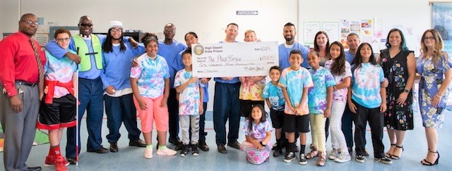 A man holds an oversized check while kids and others stand alongside him.