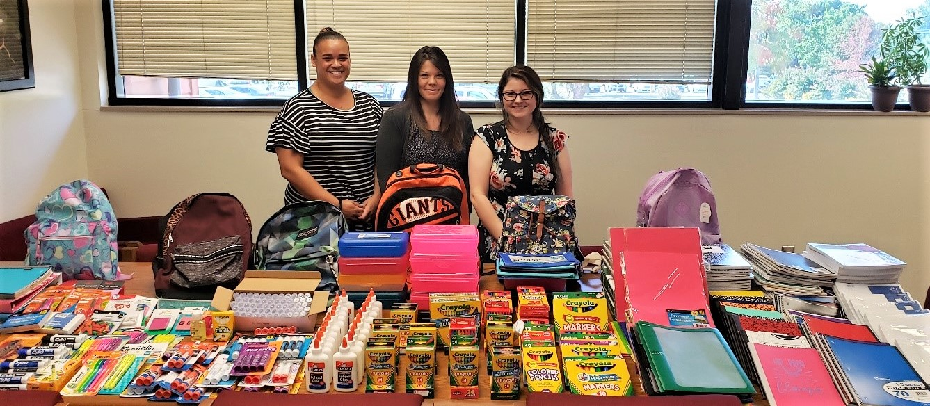 Three women stand behind table covered with notebooks, paper and other school supplies.