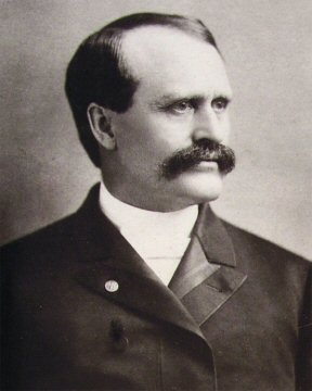 Man with big mustache and formal jacket.