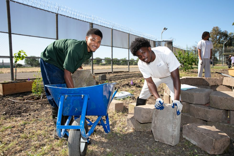 Two youth offenders lift bricks.