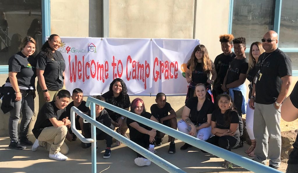 Kids and adults stand in front of a banner that says Welcome to Camp Grace.