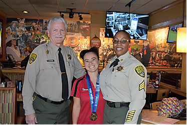 Two uniformed officers and a woman wearing a red shirt.