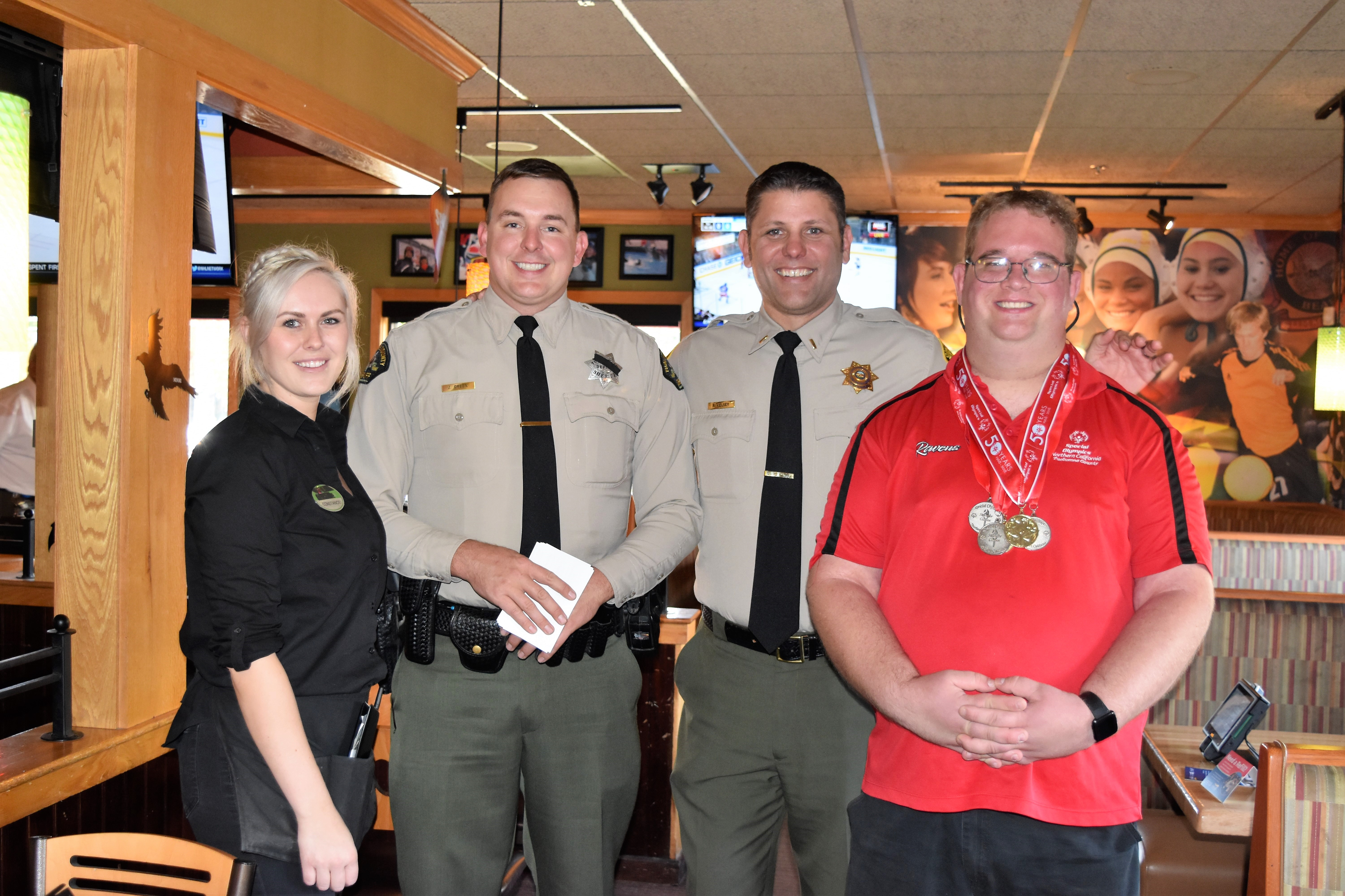 Two men in uniform are flanked by a restaurant server and a man wearing Special Olympics medals.