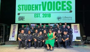 Men and women in uniform sit on a stage under the words Student Voices Est. 2018.