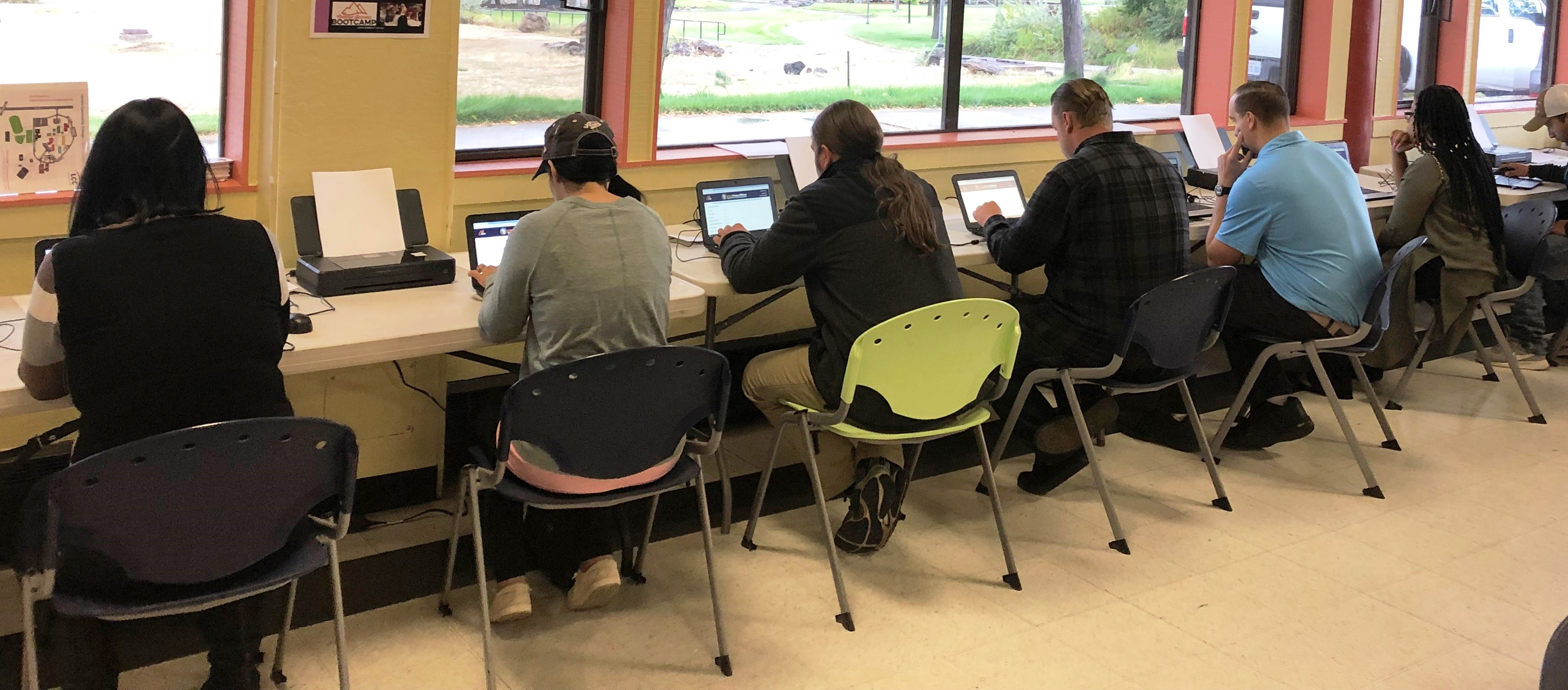 Six people sitting at computers with backs to camera