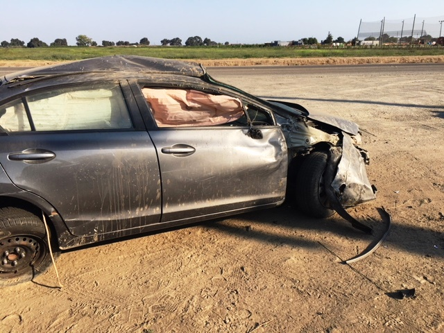 Smashed car sits in field.