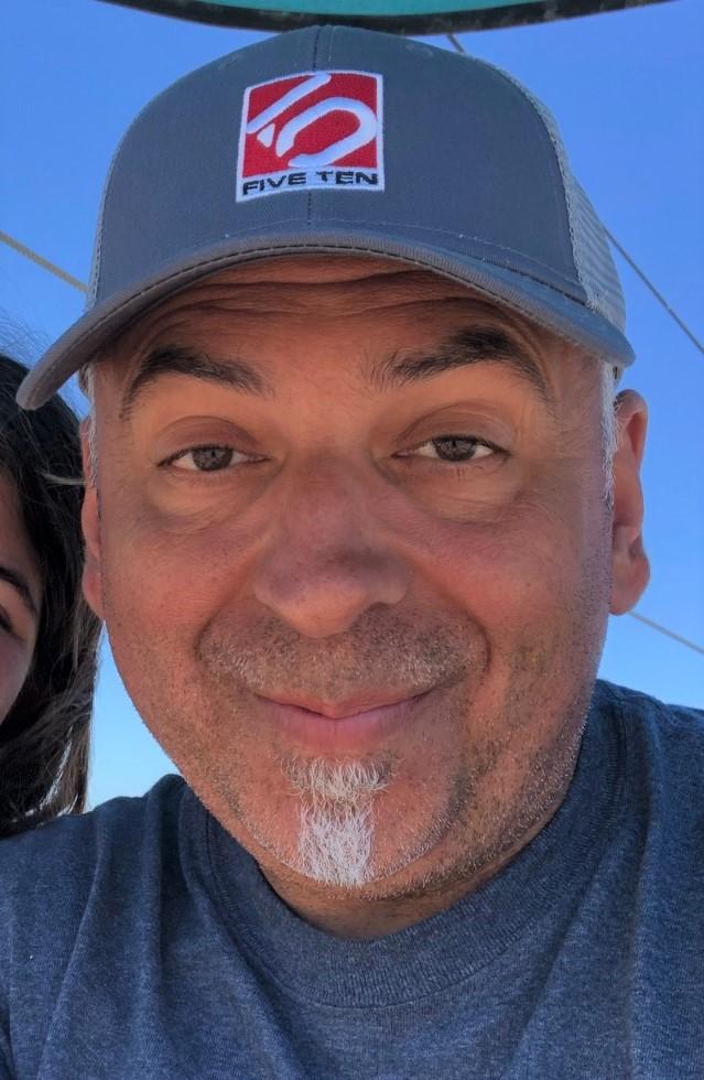 Man smiles while wearing baseball cap.