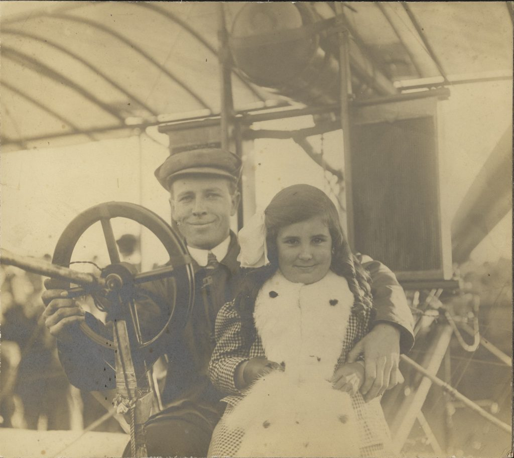 Man in old airplane sits with young girl.