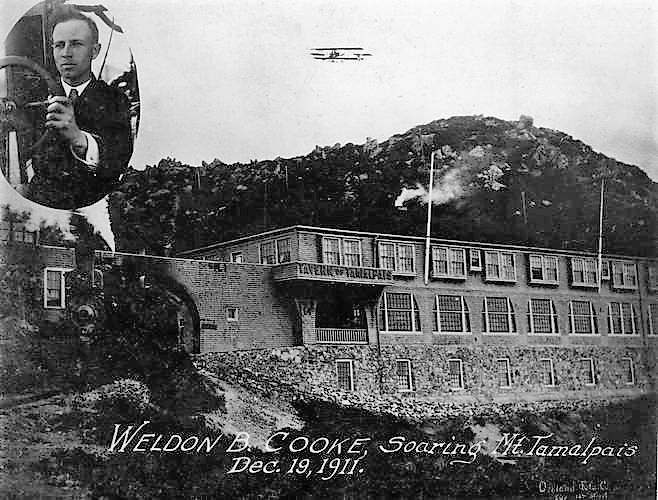 Biplane flies over building, inset photo of a man.