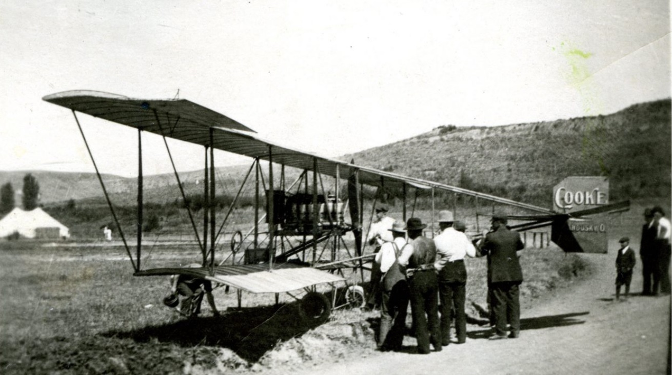 Men stand around and look at a biplane in a field.