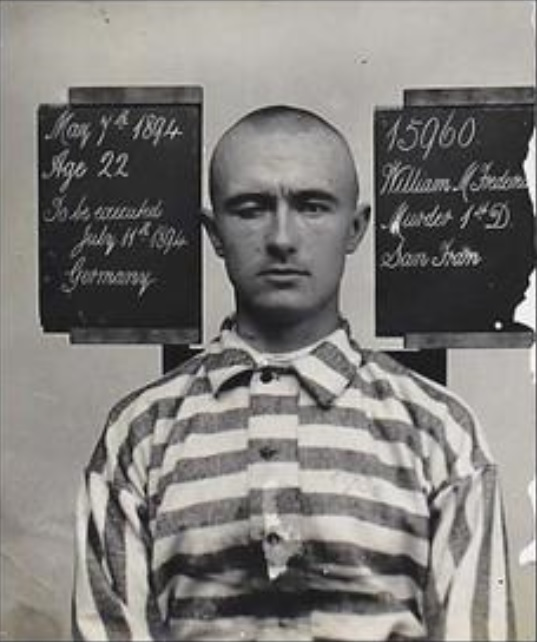 Man in prison stripes and shaved head.