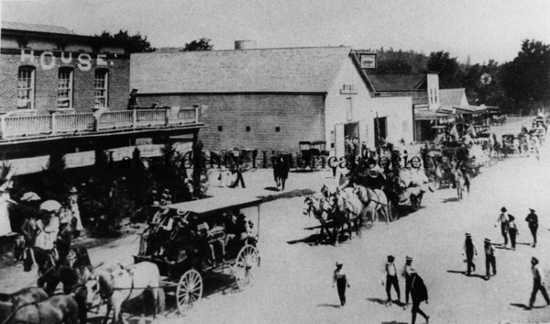 Horse-drawn carts pull a casket down a street lined with people.