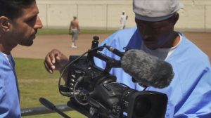 Two men in a prison yard work on a video camera.
