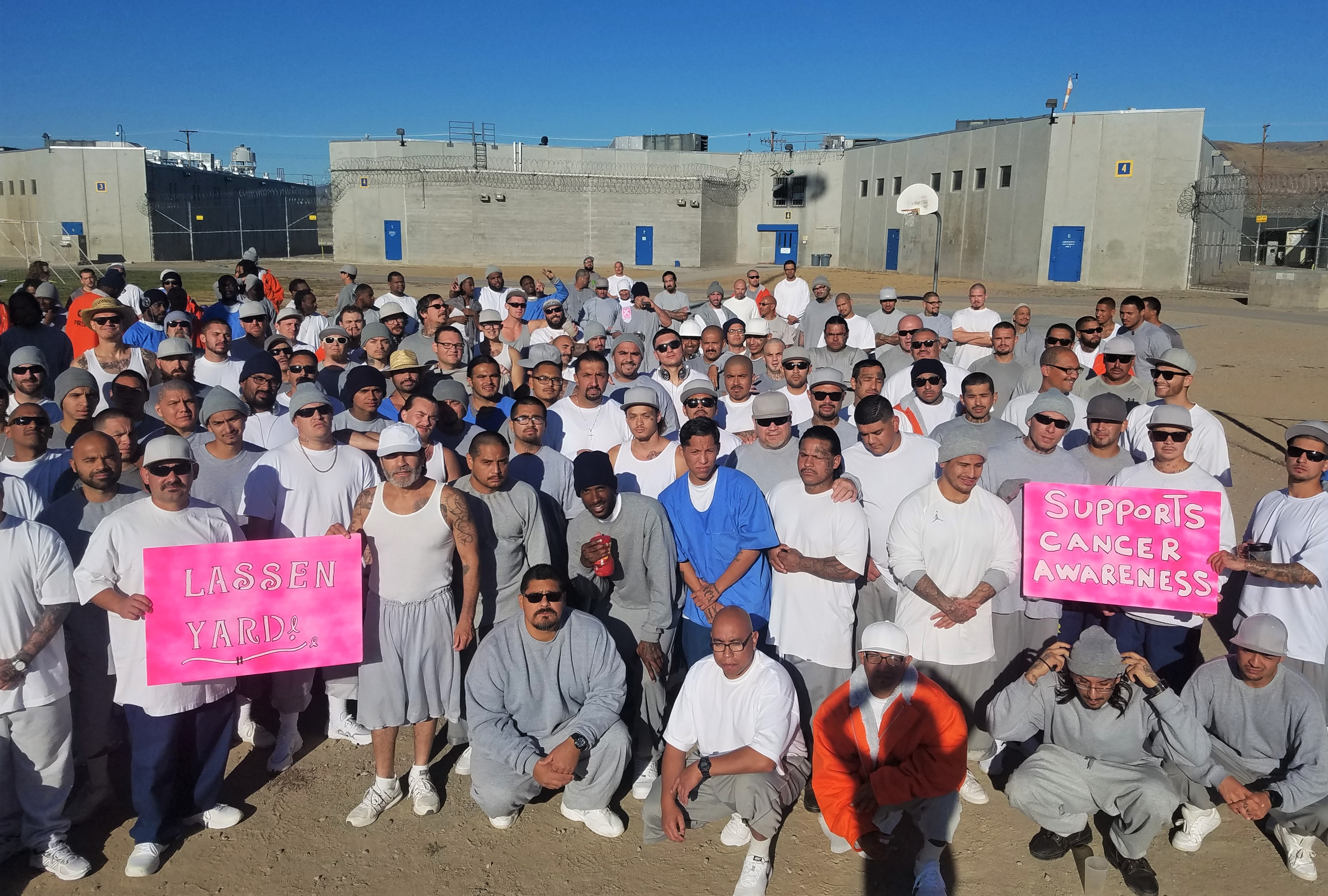 Men in a prison hold pink signs.