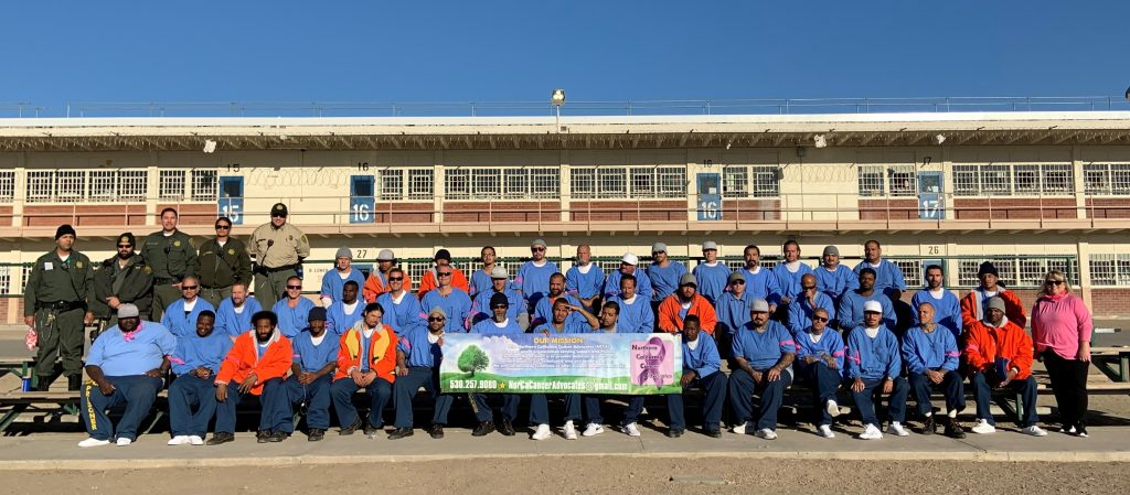 Men in blue and orange outfits stand in a prison yard, holding a banner. Correctional officers stand behind them and a woman in pink stands to the right.