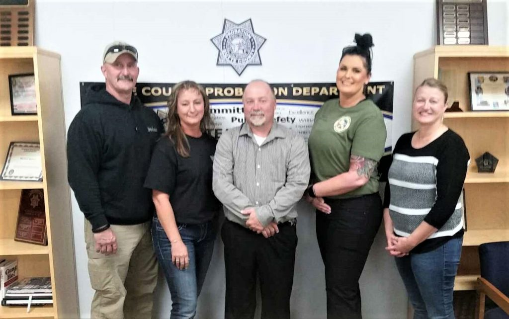Five people stand in front of a badge emblem and the words Butte County Probation Department.