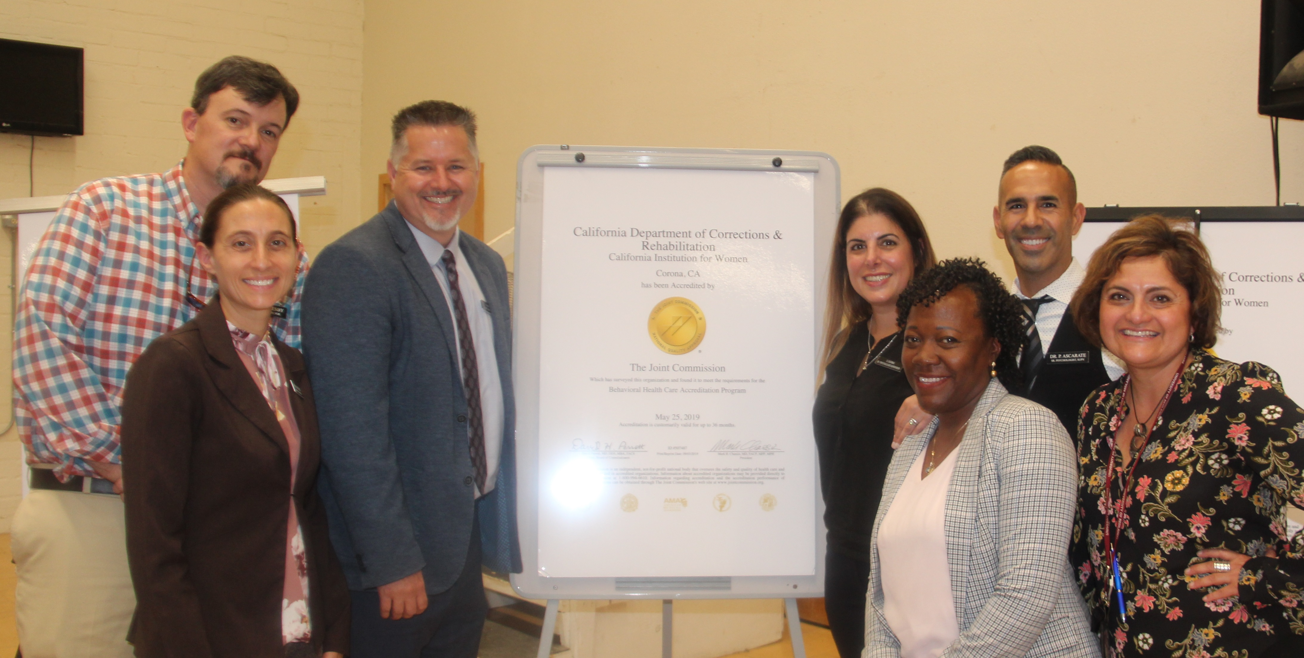 Seven people stand beside a poster recognizing the prison's health care achievement.