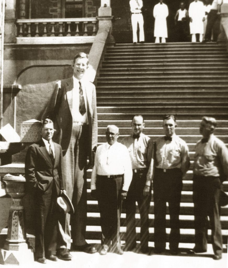 A man towers over five other men. The group is standing in front of stairs.