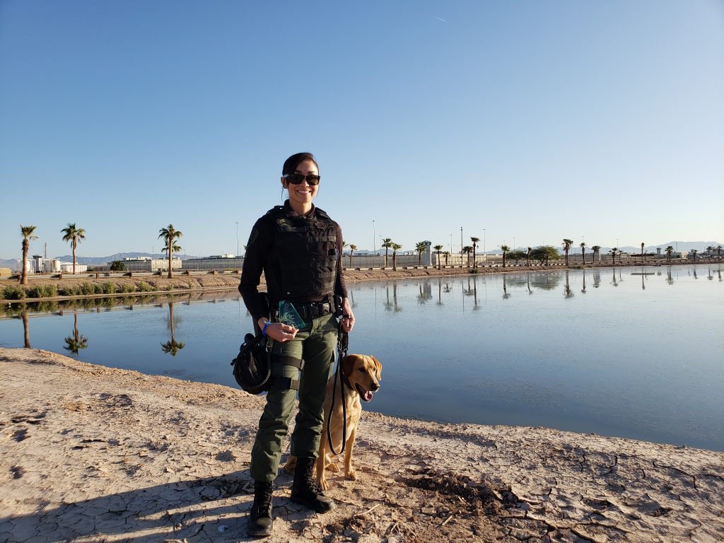 Officer Lupe Gutierrez standing and holder a lease to K-9 Dexter by the lake