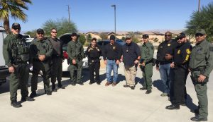 Men and women in uniform prepare to sweep neighborhoods checking on offenders.
